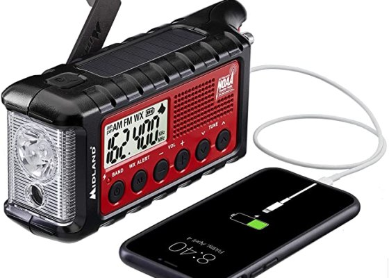 A Midland NOAA weather radio with hand crank and solar panel. It is charging an iPhone.