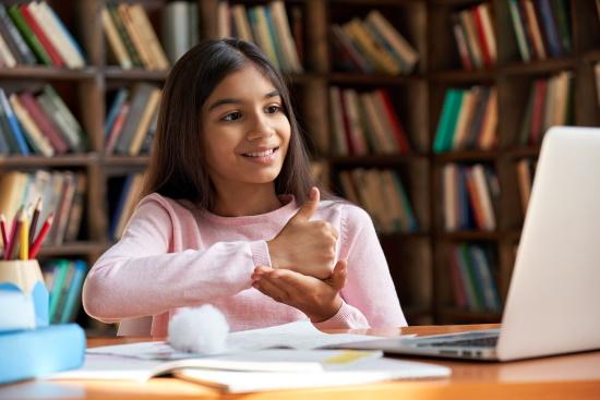 A girl using sign language and facing a laptop computer.