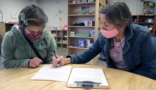 Two women work together at a table wearing masks, one assisting the other, eyes cast on paperwork.
