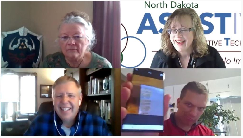 Grid of four images of Zoom participants including an older adult woman, a smiling ND Assistive staff person (woman), a man smiling wearing earbuds, and a man holding up his mobile device to the webcam.